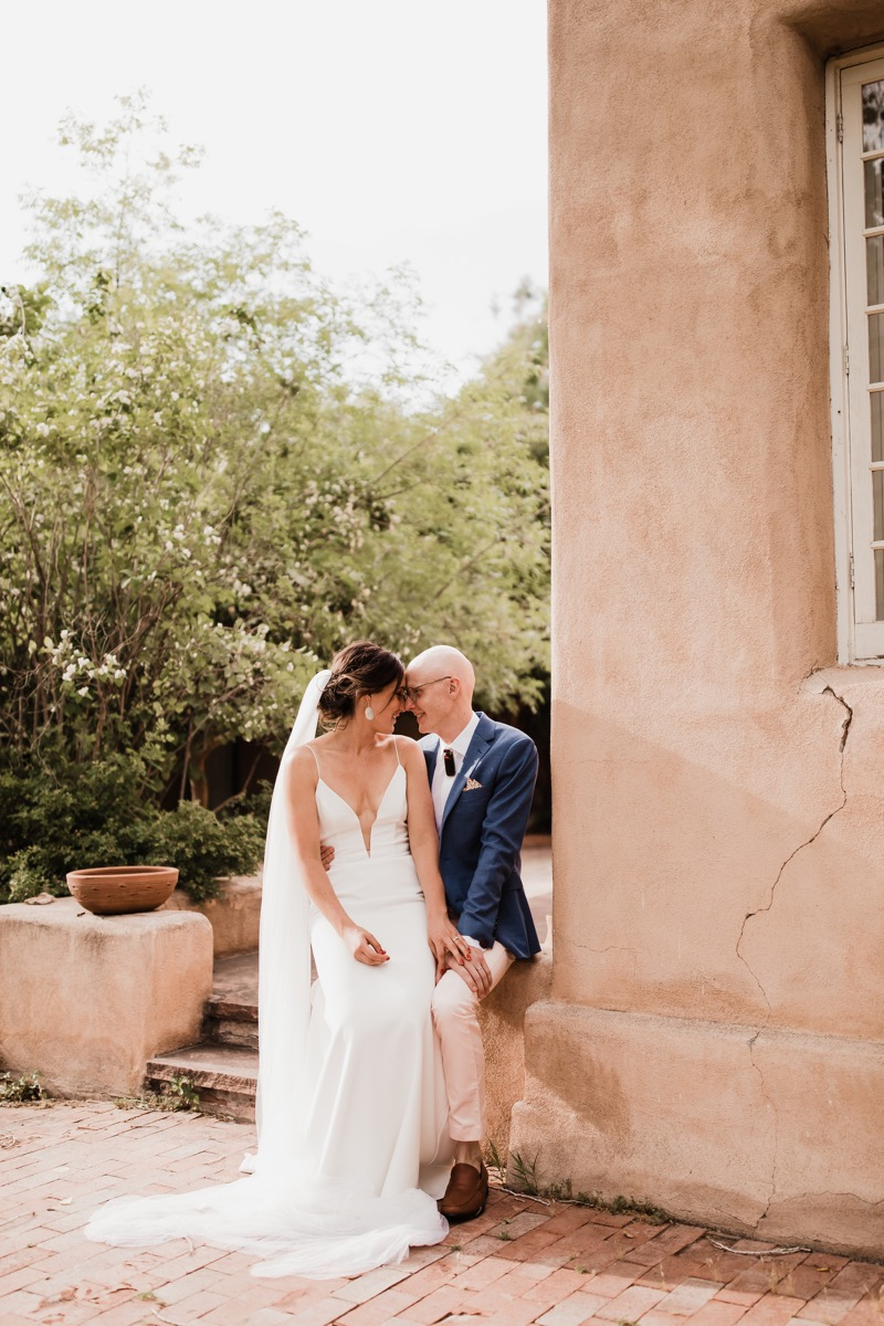 lAVENDER FARM WEDDING ALBUQUERQUE NEW MEXICO ALICIA LUCIA PHOTOGRAPHY CARA ON QWIST'S LAP BY OLD BUILDING