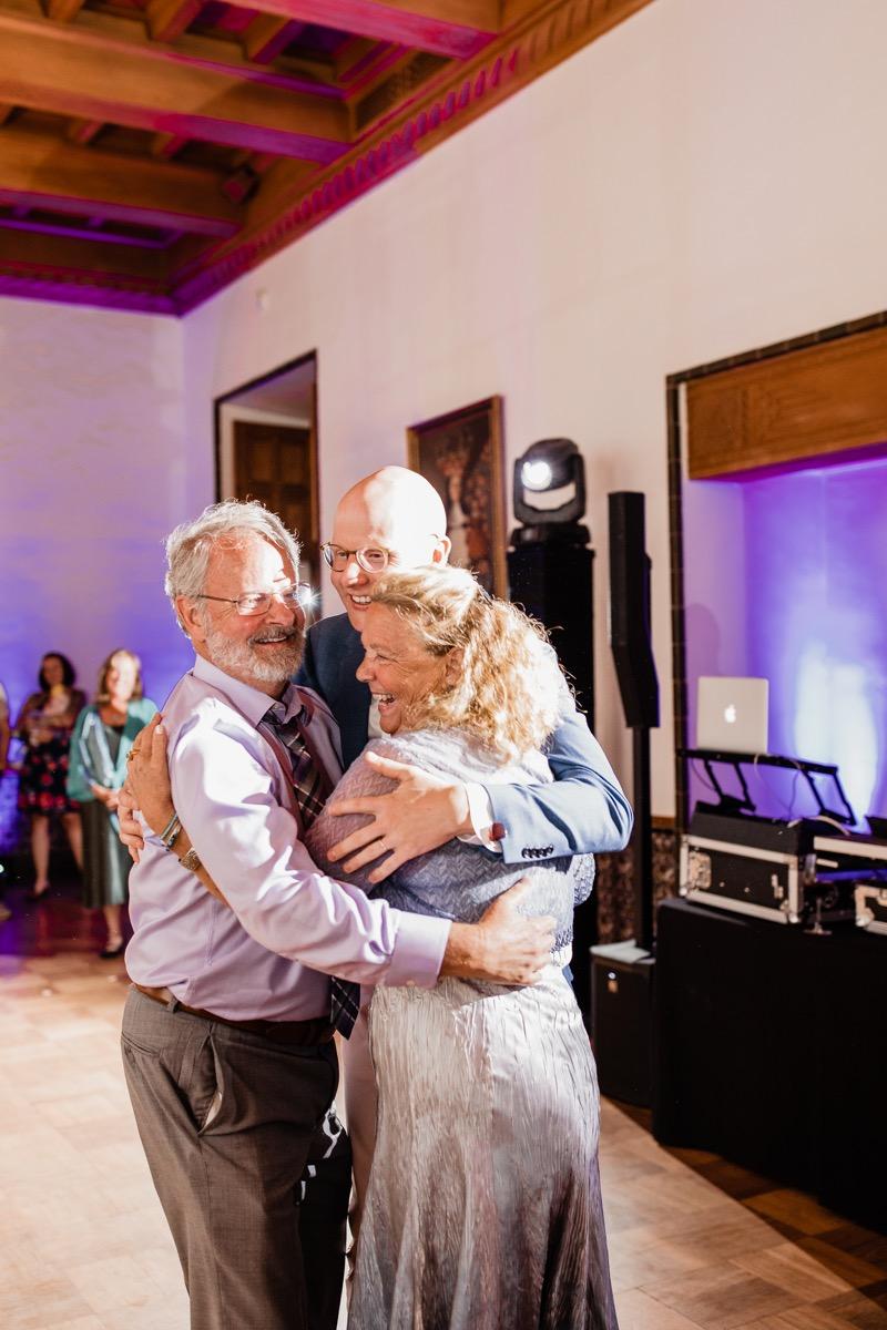 lAVENDER FARM WEDDING ALBUQUERQUE NEW MEXICO ALICIA LUCIA PHOTOGRAPHY QWIST AND PARENTS HUG ON DANCE FLOOR