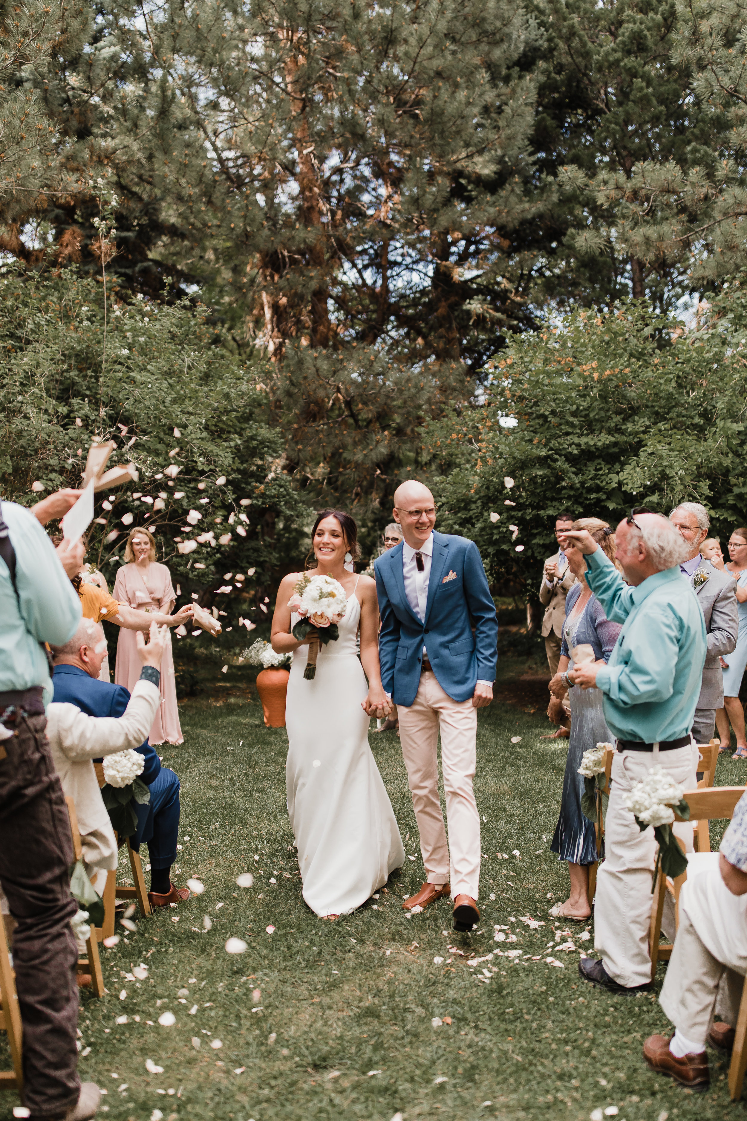 lAVENDER FARM WEDDING ALBUQUERQUE NEW MEXICO ALICIA LUCIA PHOTOGRAPHY GUESTS THROWING PETALS AS COUPLE LEAVES WEDDING CEREMONY