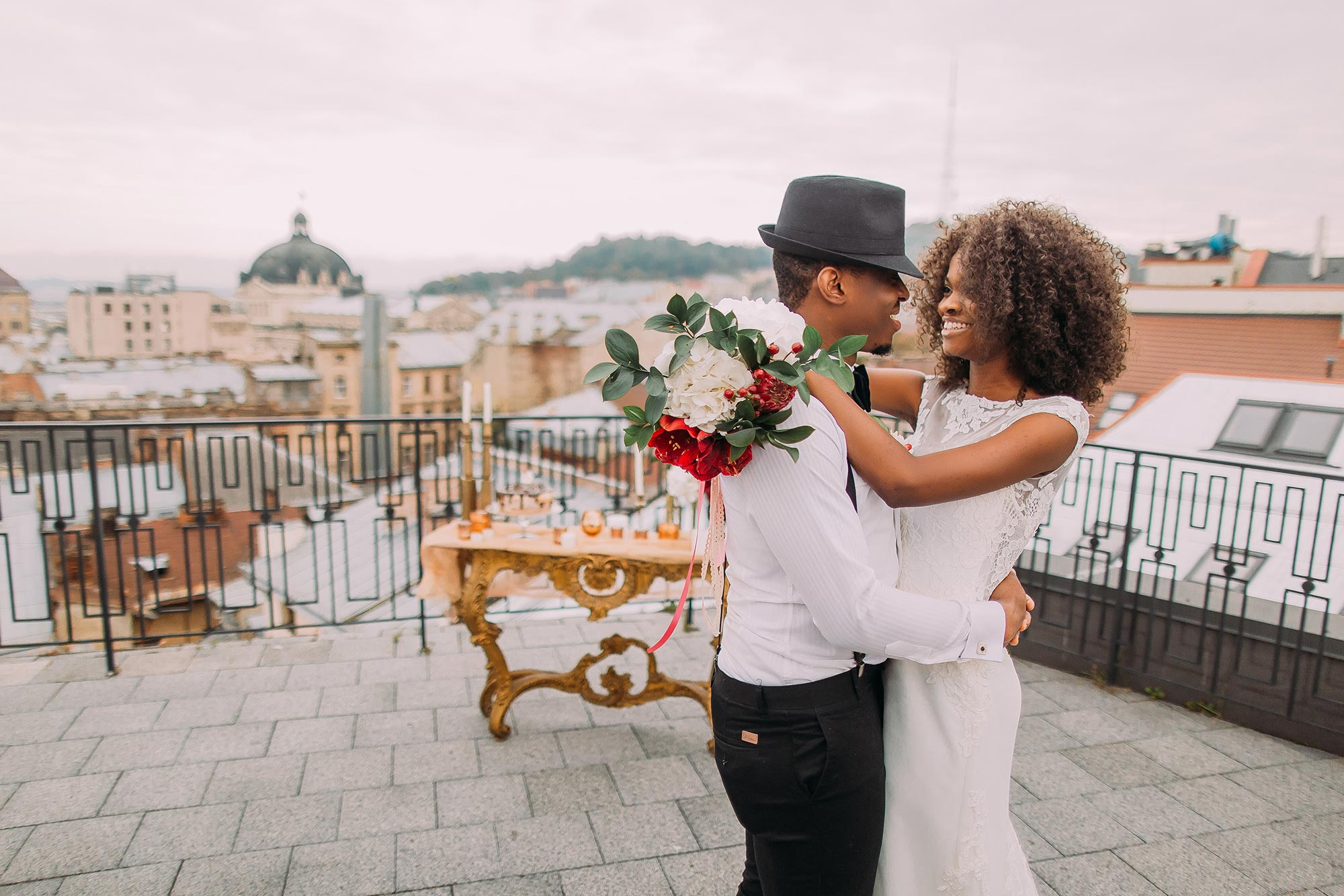 newlywed couple in an embrace on rooftop