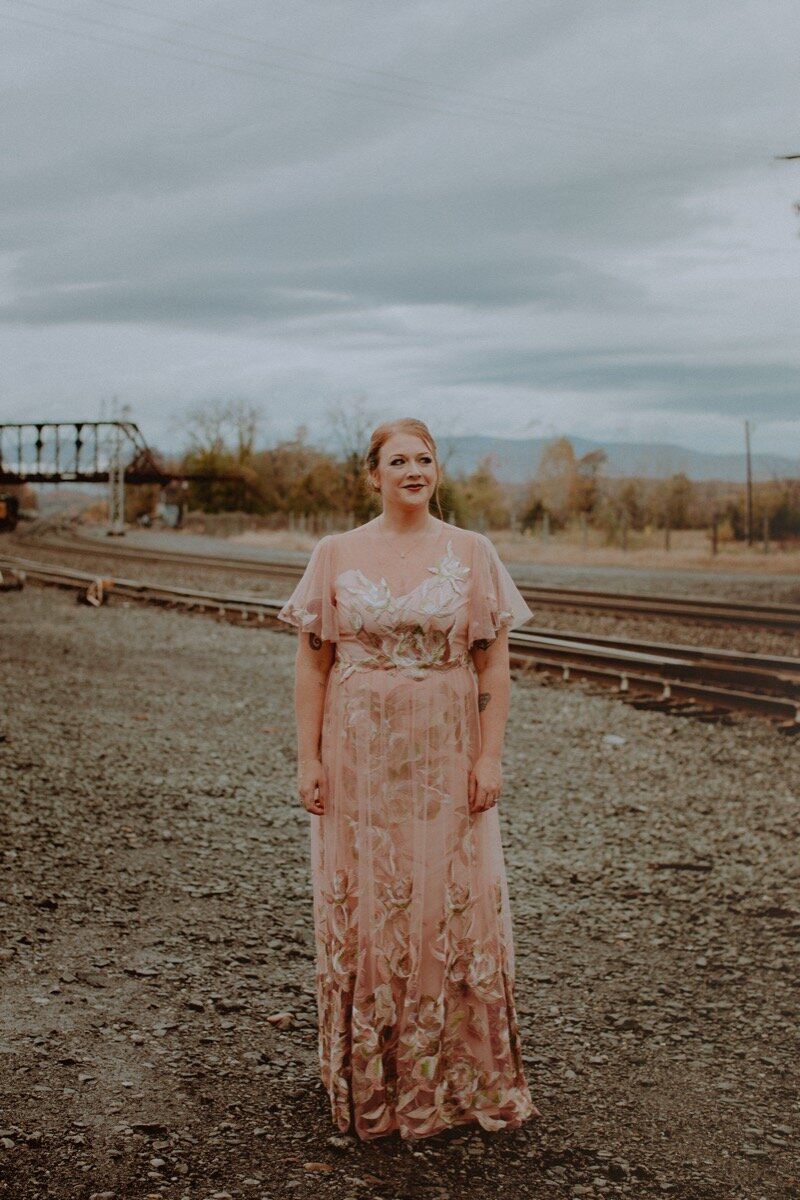 bride in pink lace chiffon dress near old train tracks before industrial wedding ceremony in Hudson New York Chellise Michael Photography