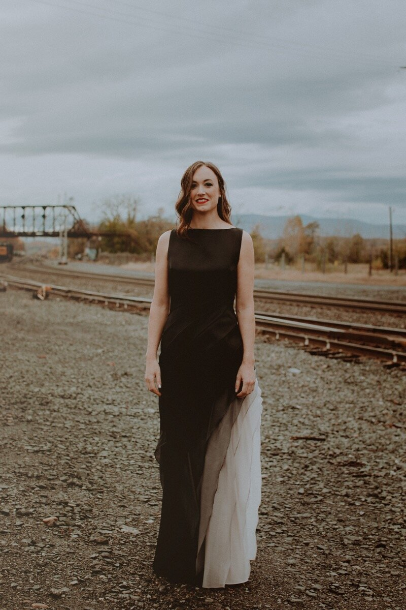 bride in black and white dress near old train tracks before industrial wedding ceremony in Hudson New York Chellise Michael Photography