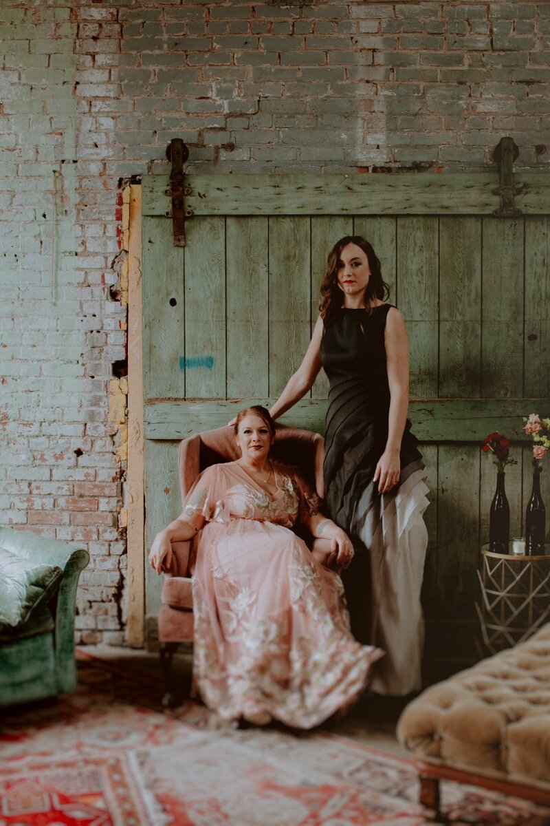brides pose for portrait in vintage chairs at industrial wedding venue in Hudson New York Chellise Michael Photography