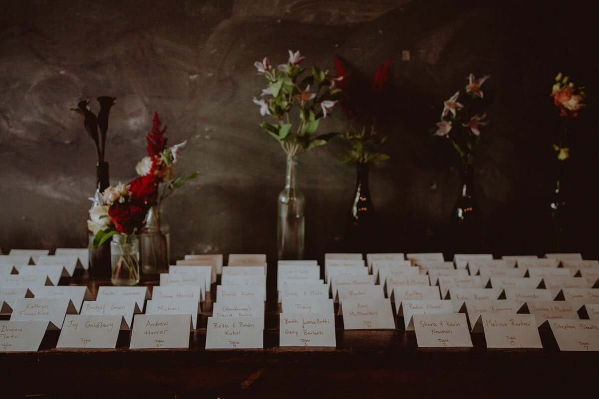 Escort cards and flowers at reception at industrial wedding venue in Hudson New York Chellise Michael Photography