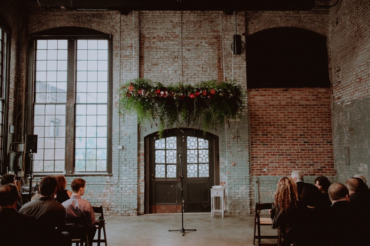 Floral canopy over ceremony spot at industrial wedding venue in Hudson New York Chellise Michael Photography