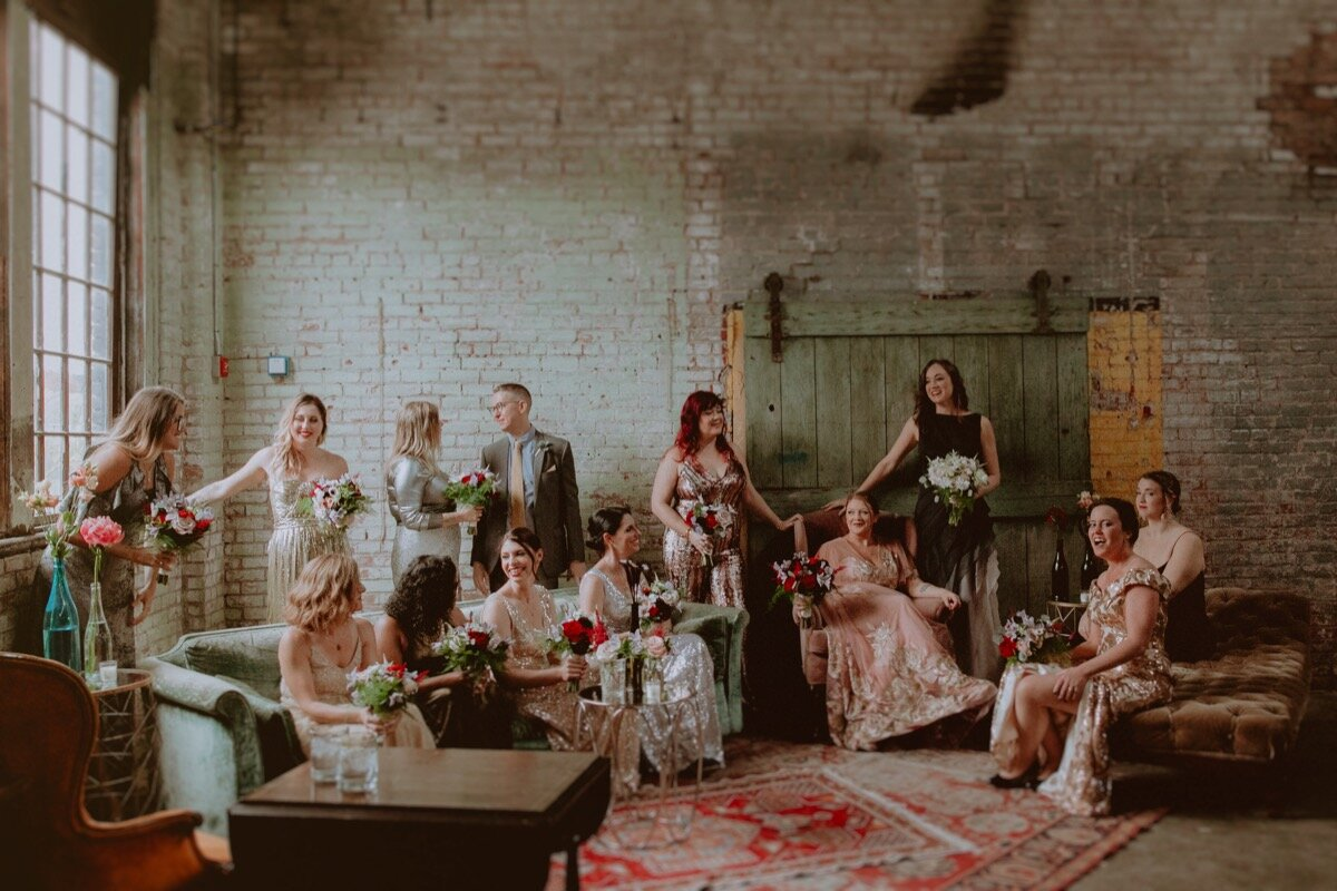 brides and wedding party sit in vintage chairs at industrial wedding venue in Hudson New York Chellise Michael Photography