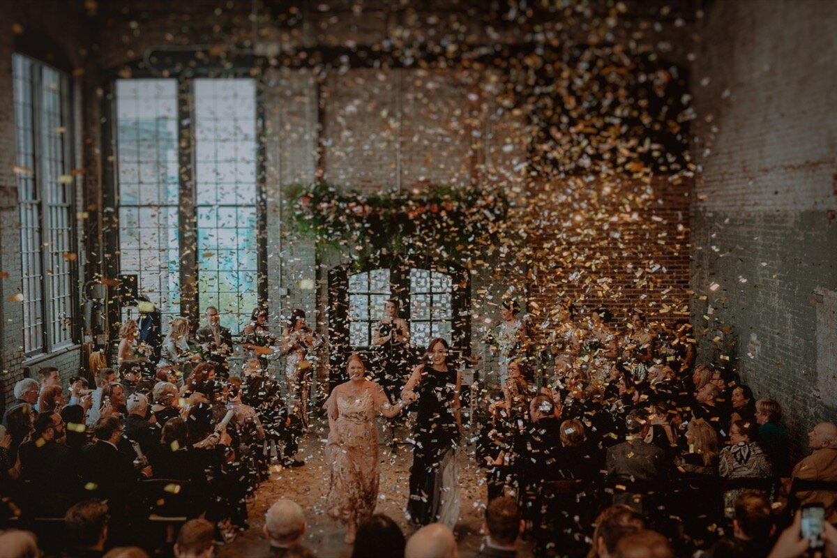 Confetti in air during ceremony recessional at industrial wedding venue in Hudson New York Chellise Michael Photography