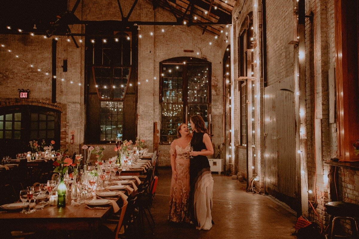 Brides smile while looking at reception tables at industrial wedding venue in Hudson New York Chellise Michael Photography
