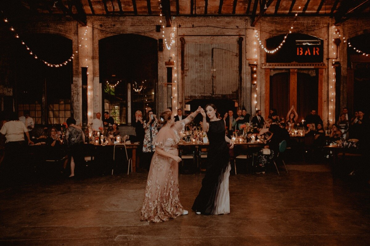 Brides during first dance at reception at industrial wedding venue in Hudson New York Chellise Michael Photography