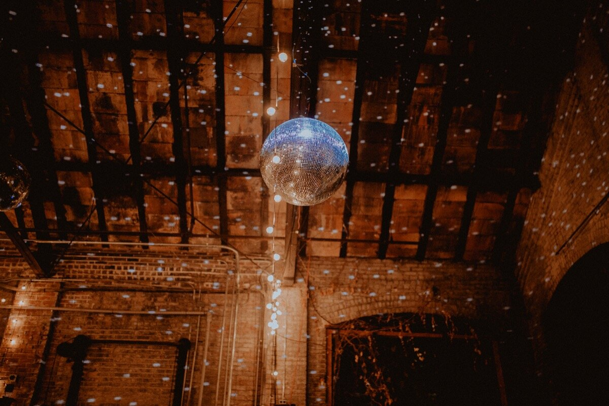 Disco ball over dance floor at reception at industrial wedding venue in Hudson New York Chellise Michael Photography