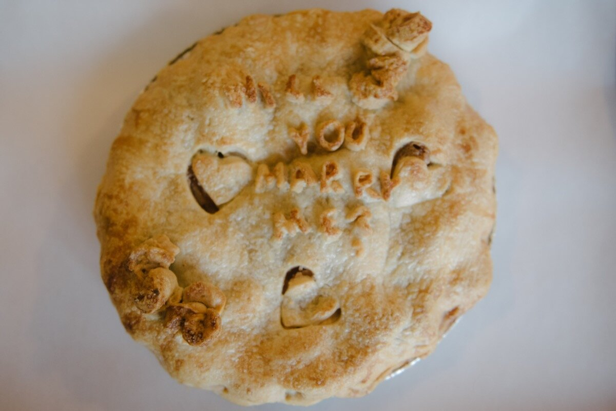 """Pie that reads """"will you marry me?"""" for surprise proposal at sugar bakeshop denver colorado Friends and Lovers Photography"""