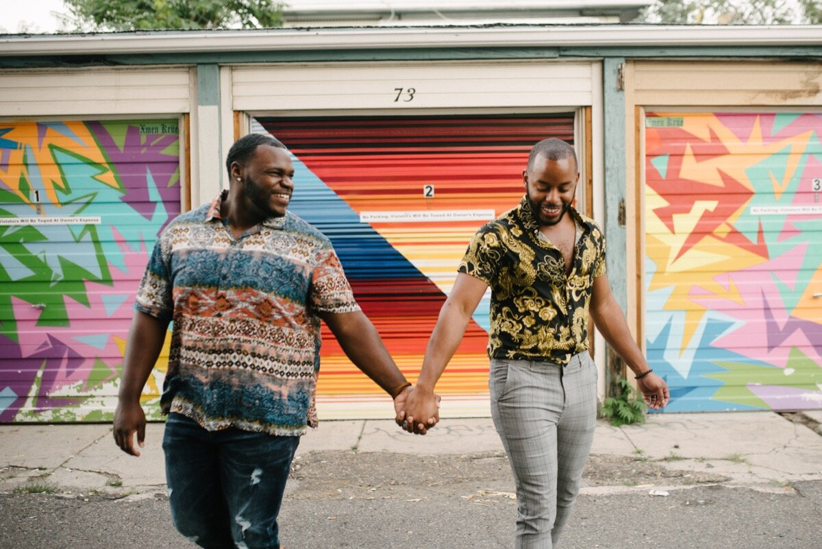 Chris and Nate hold hands by mural wall after surprise proposal at sugar bakeshop denver colorado Friends and Lovers Photography