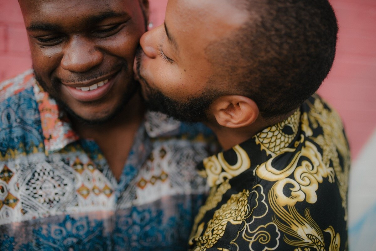 Chris and Nate kiss on cheek after surprise proposal at sugar bakeshop denver colorado Friends and Lovers Photography