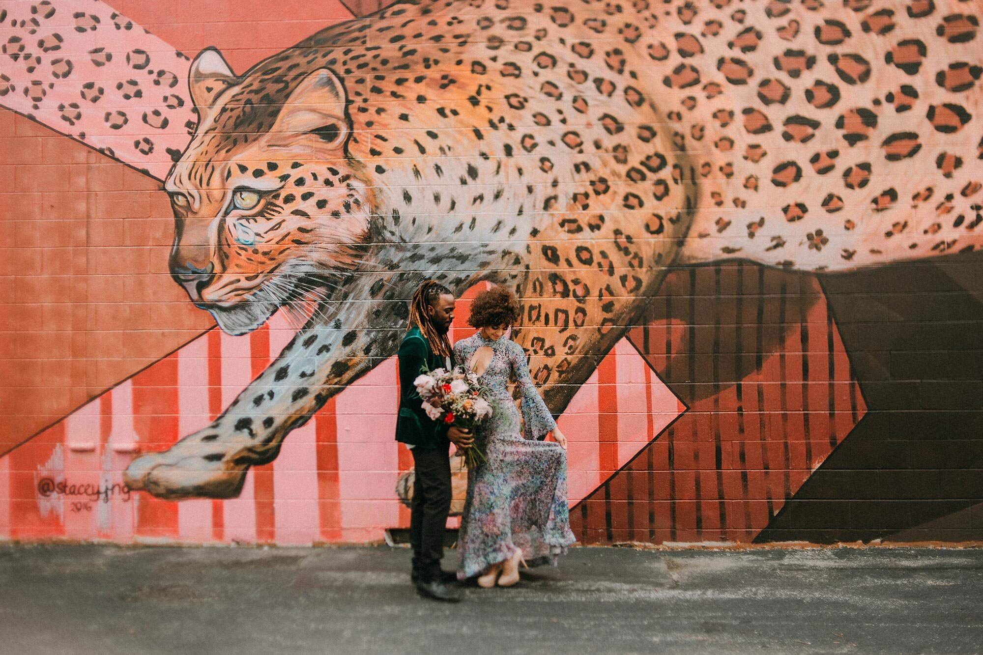 bride in sequin dress and groom in green velvet suit in front of leopard mural Milwaukee A Lentz Photography