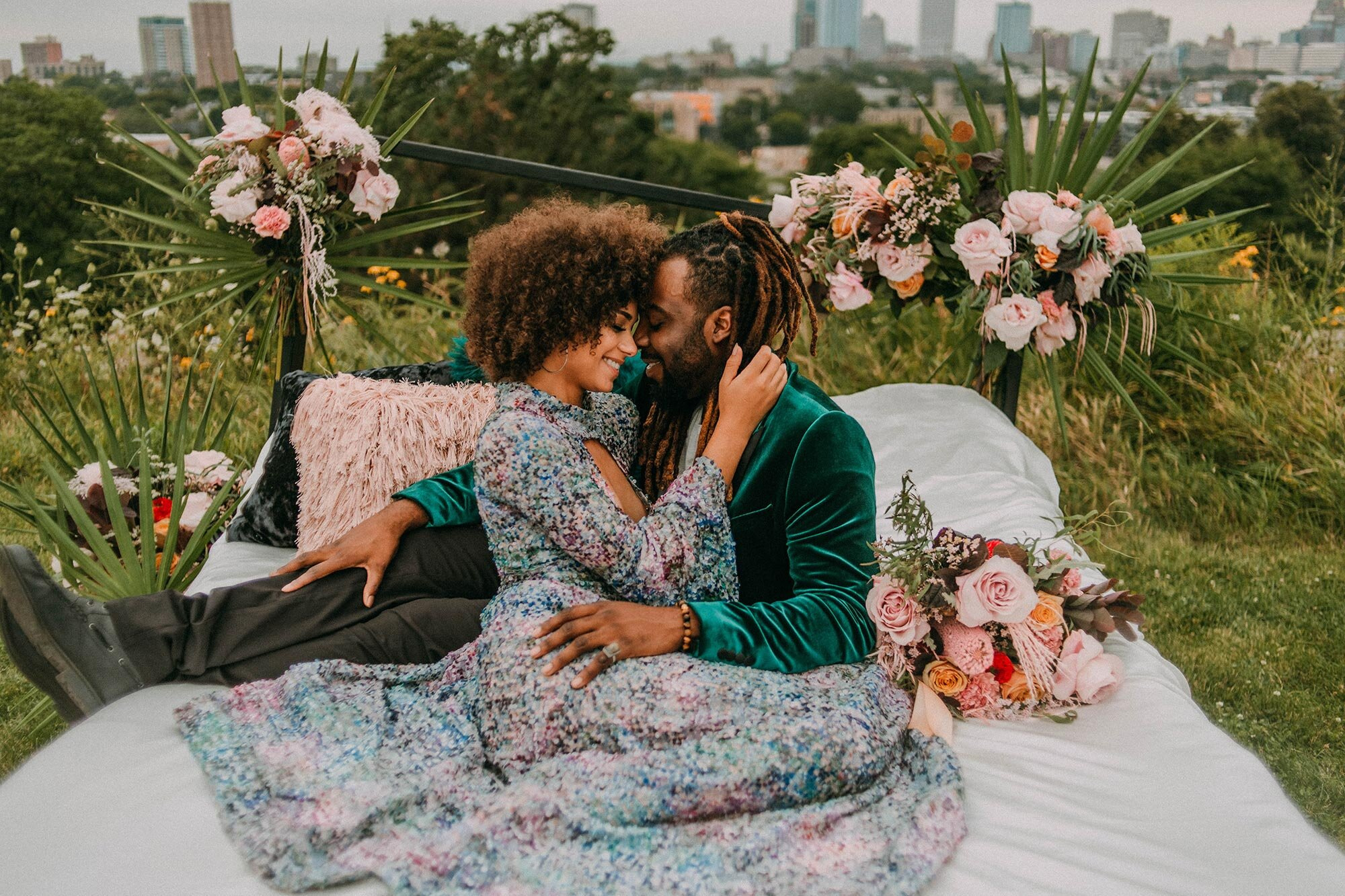 bride in sequin dress and groom in green velvet suit embraces on bed surrounded by grass and flowers wedding elopement inspiration Milwaukee A Lentz Photography