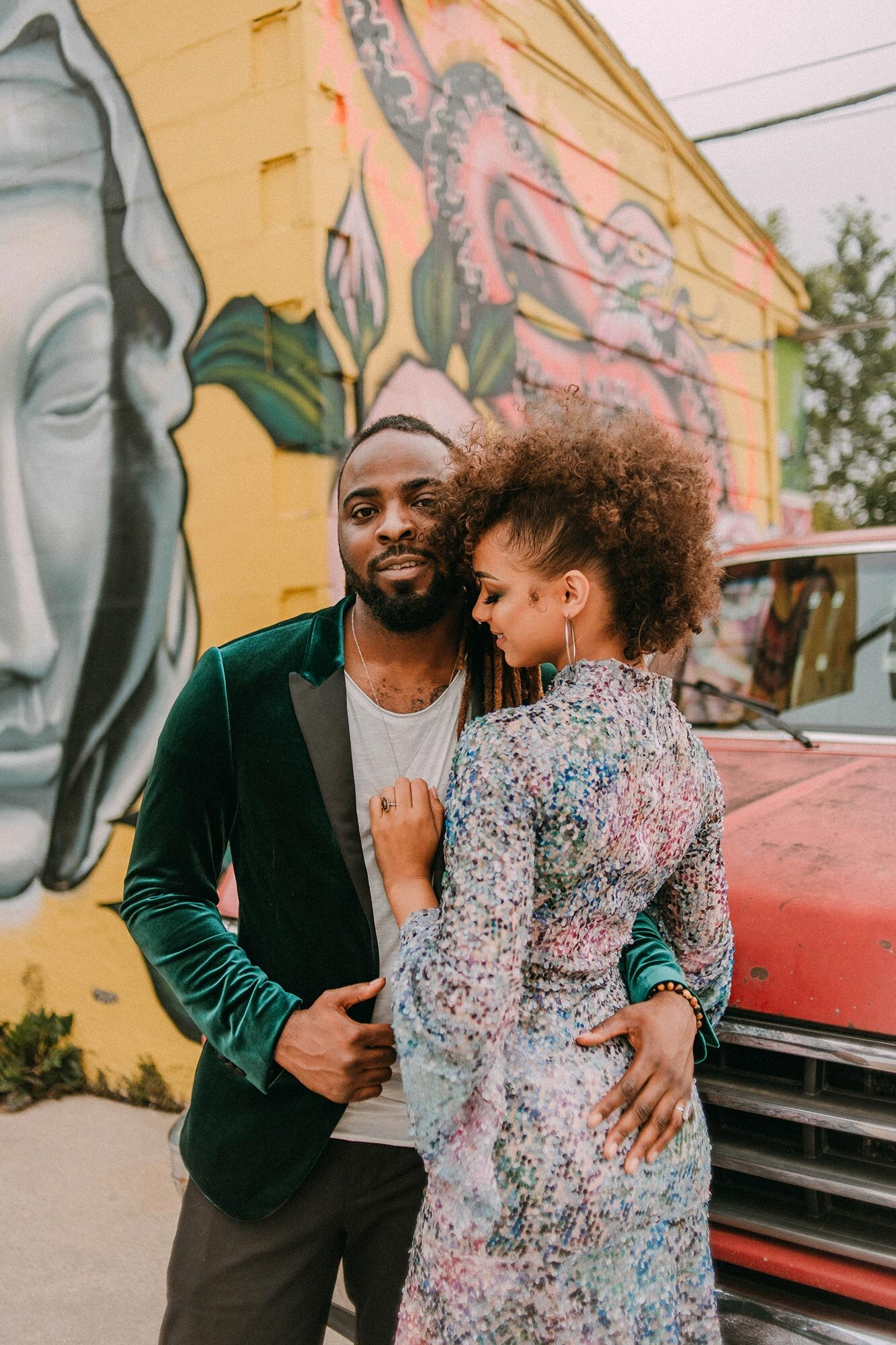 bride in sequin dress and groom in green velvet suit embraces in front of red truck and mural wall wedding elopement inspiration Milwaukee A Lentz Photography