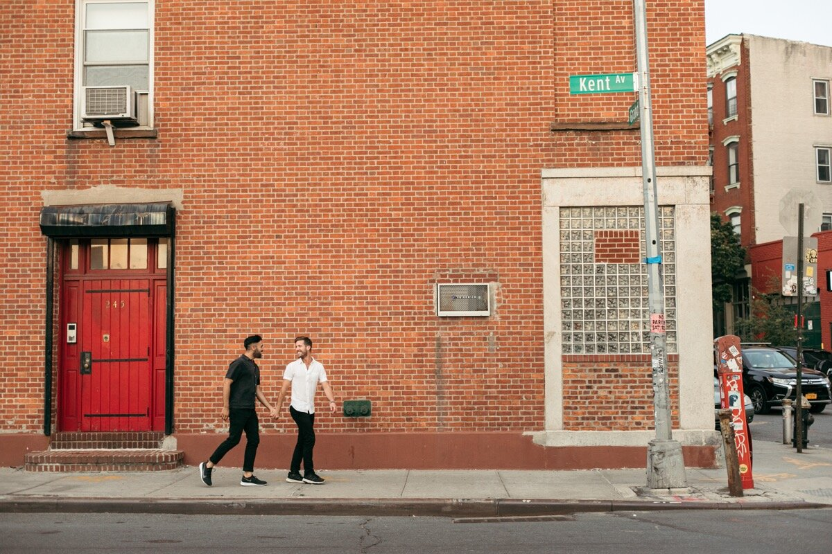 Joe and Rohan walk down the sidewalk holding hands during couples photo session in Domino Park Brooklyn Bailey Q Photo