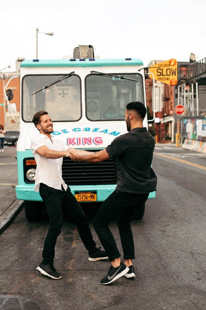 Joe and Rohan twirl around holding hands in front of ice cream truck during couples photo session in Domino Park Brooklyn Bailey Q Photo