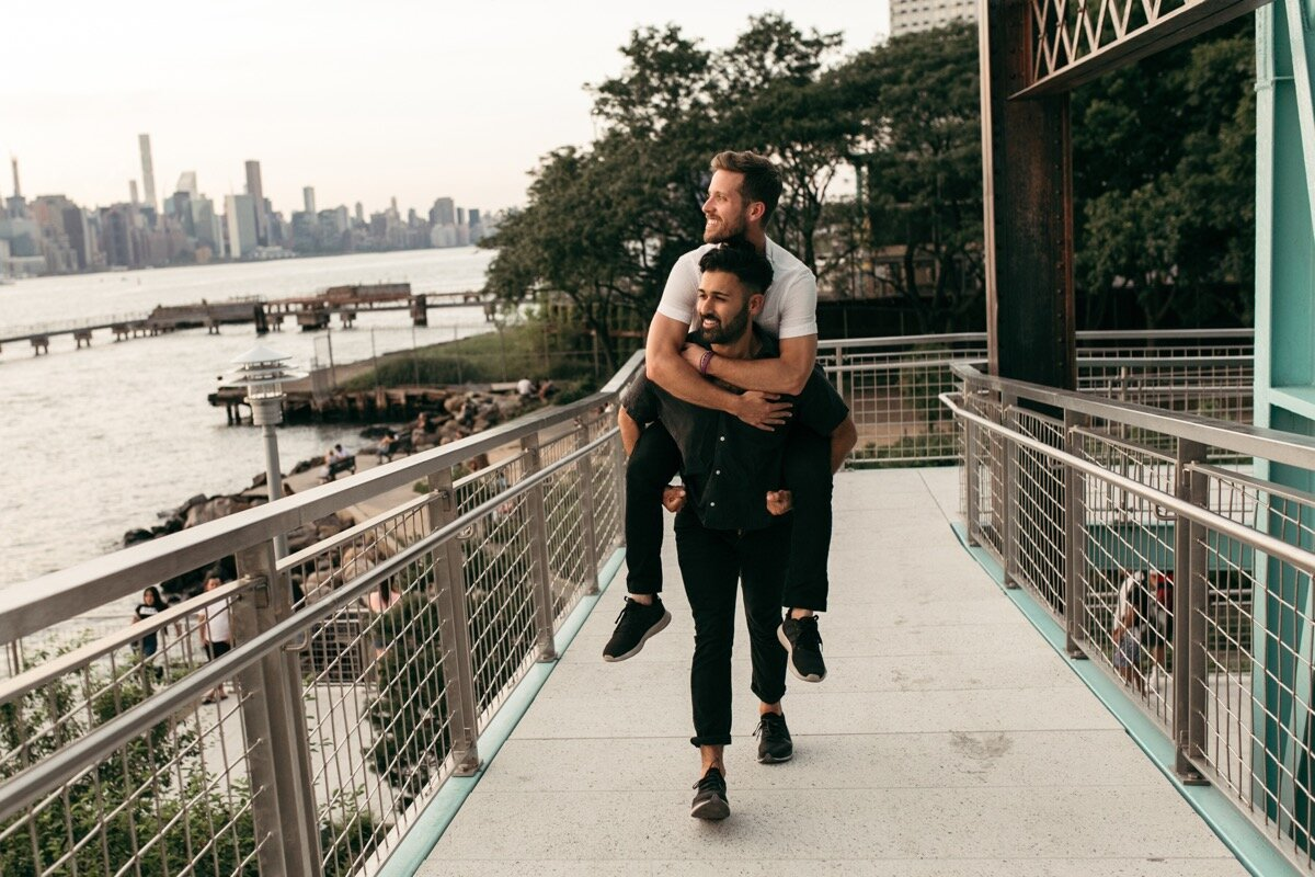 Rohan carried Joe on his back across bridge during couples photo session in Domino Park Brooklyn Bailey Q Photo