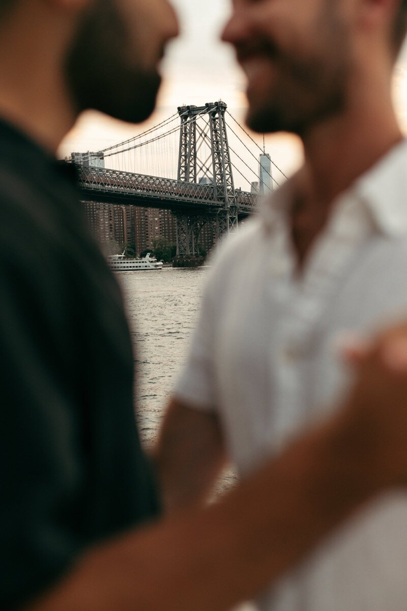 Joe and Rohan embrace with bridge in background during couples photo session in Domino Park Brooklyn Bailey Q Photo