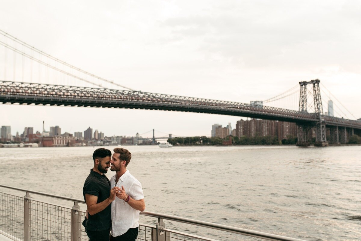 Joe and Rohan dance together by waterfront with bridge in background during couples photo session in Domino Park Brooklyn Bailey Q Photo
