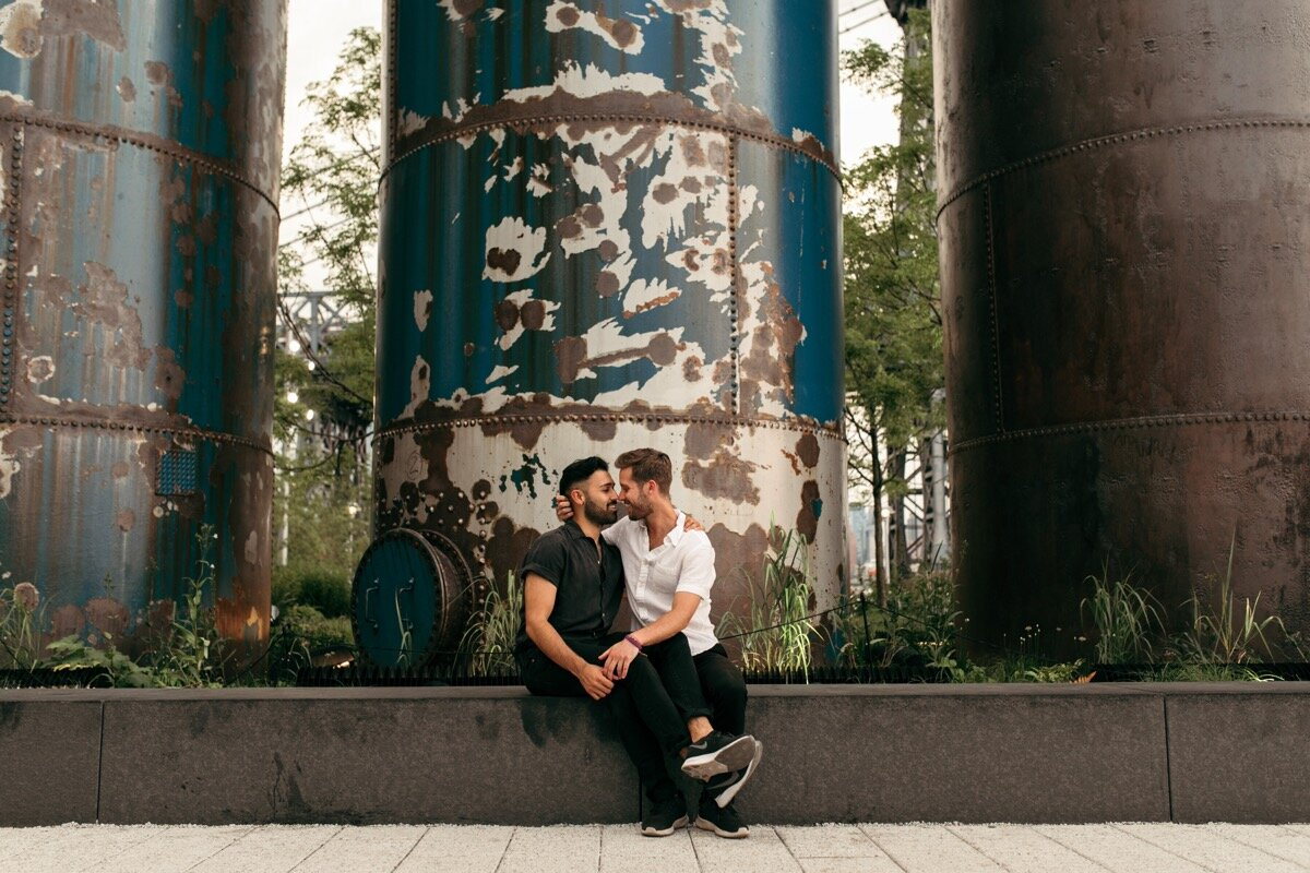 Joe and Rohan snuggle up together in front of industrial silos during couples photo session in Domino Park Brooklyn New York Bailey Q Photo