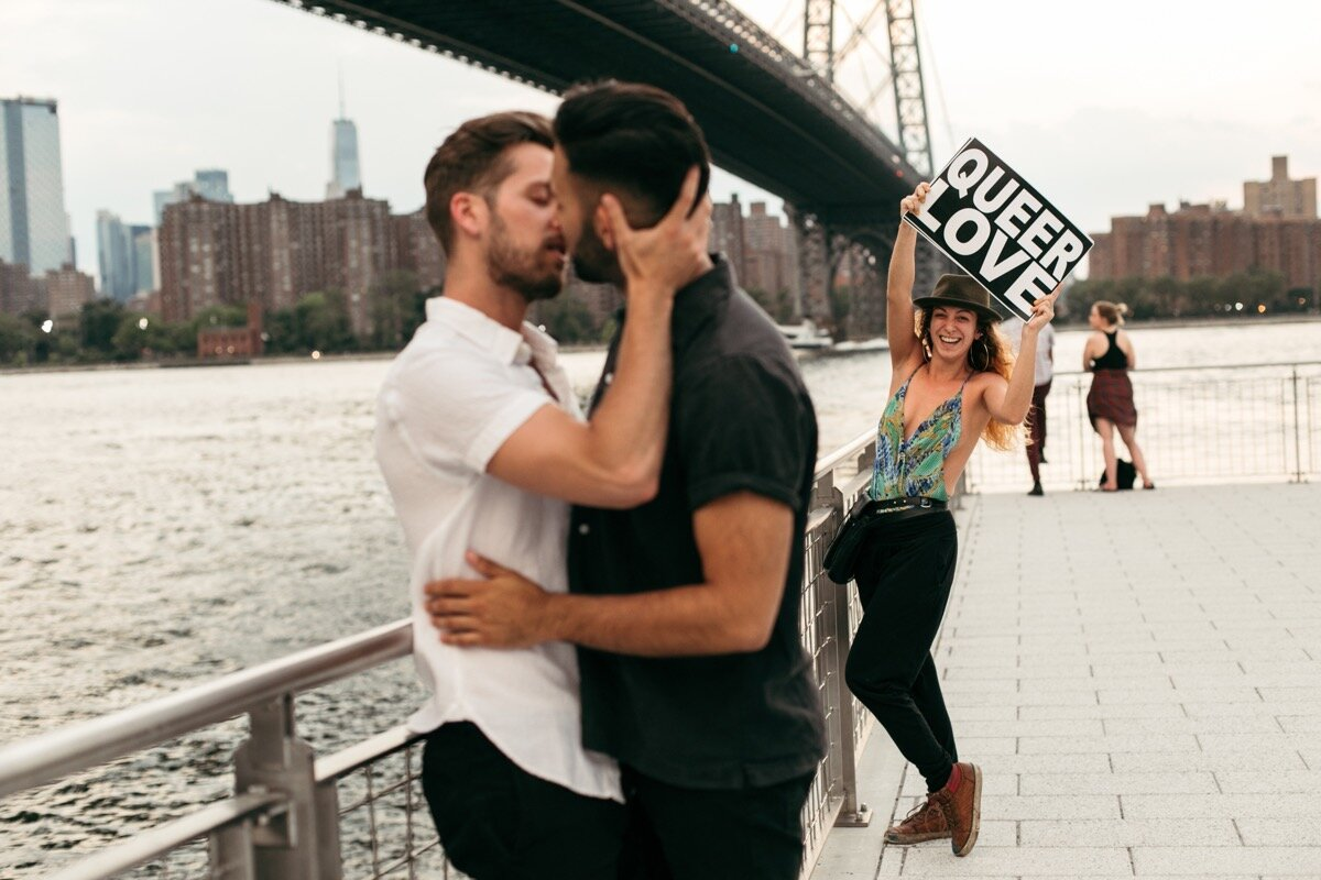 """Joe and Rohan kiss along the waterfront while passerby holds sign that says """"Queer Love"""" during couples photo session in Domino Park Brooklyn New York Bailey Q Photo"""