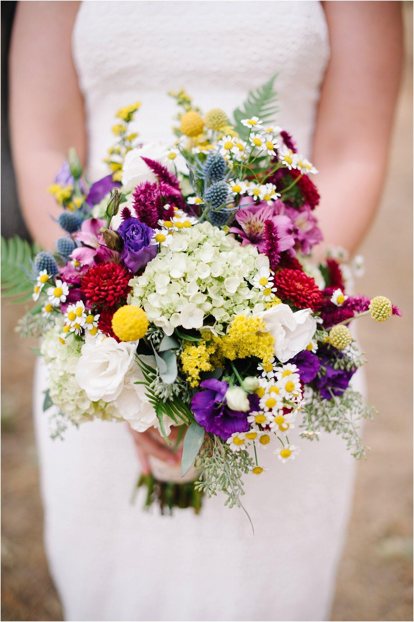 bride holding colorful bouquet at cozy campsite wedding in portland oregon