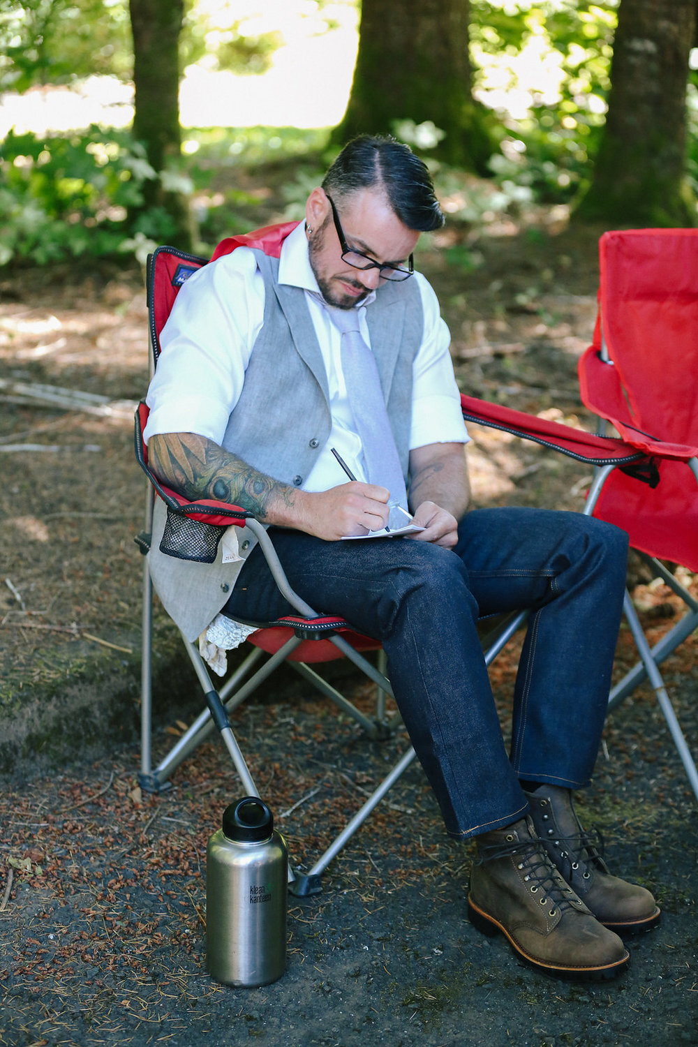 writing vows in a camping chair before campsite wedding in oregon