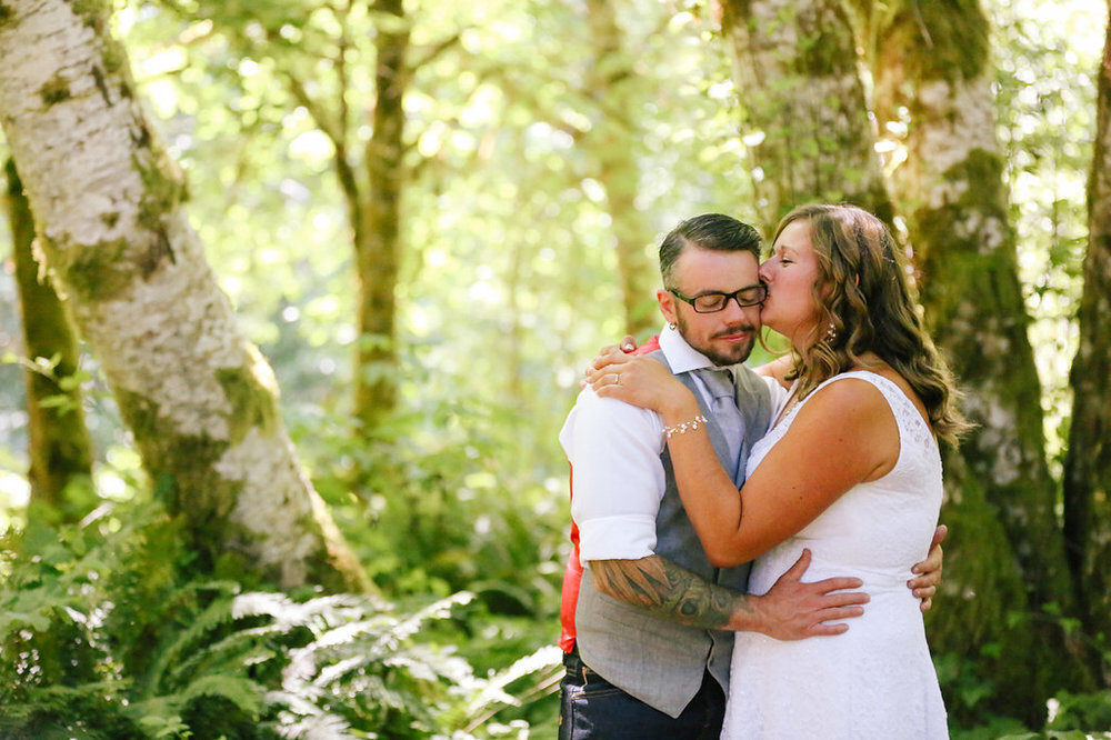 PK and Korel kiss and embrace in the woods at their campsite wedding in Oregon