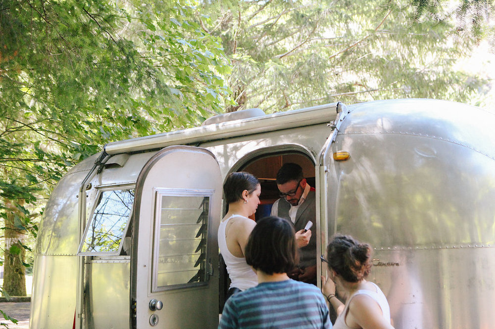 PK and Korel getting ready for wedding in airstream trailer at campsite wedding in oregon