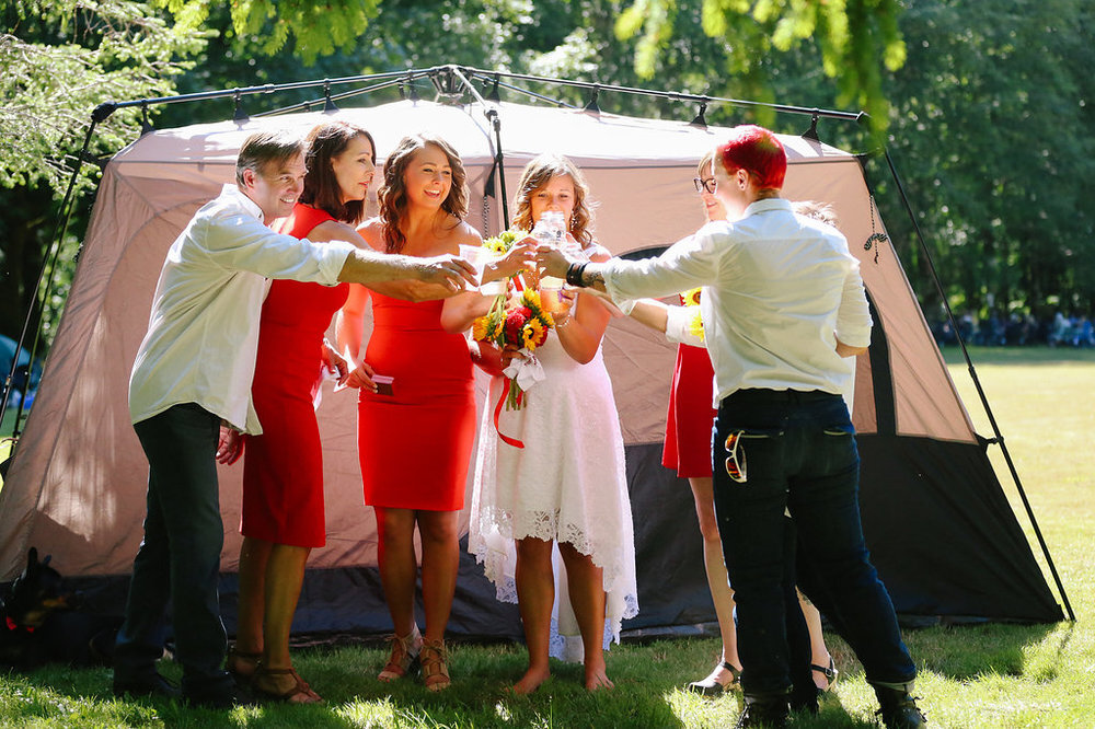 wedding party toast to the newlywed couple outside tent at campsite wedding in Oregon