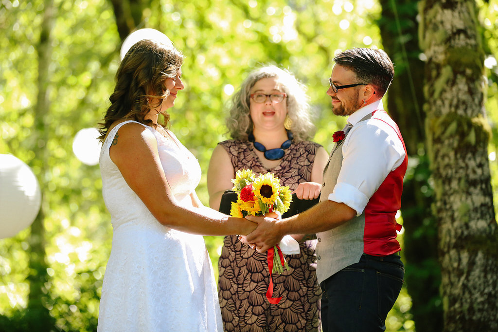PK and Korel exchanging vows during their wedding ceremony at campsite in Oregon
