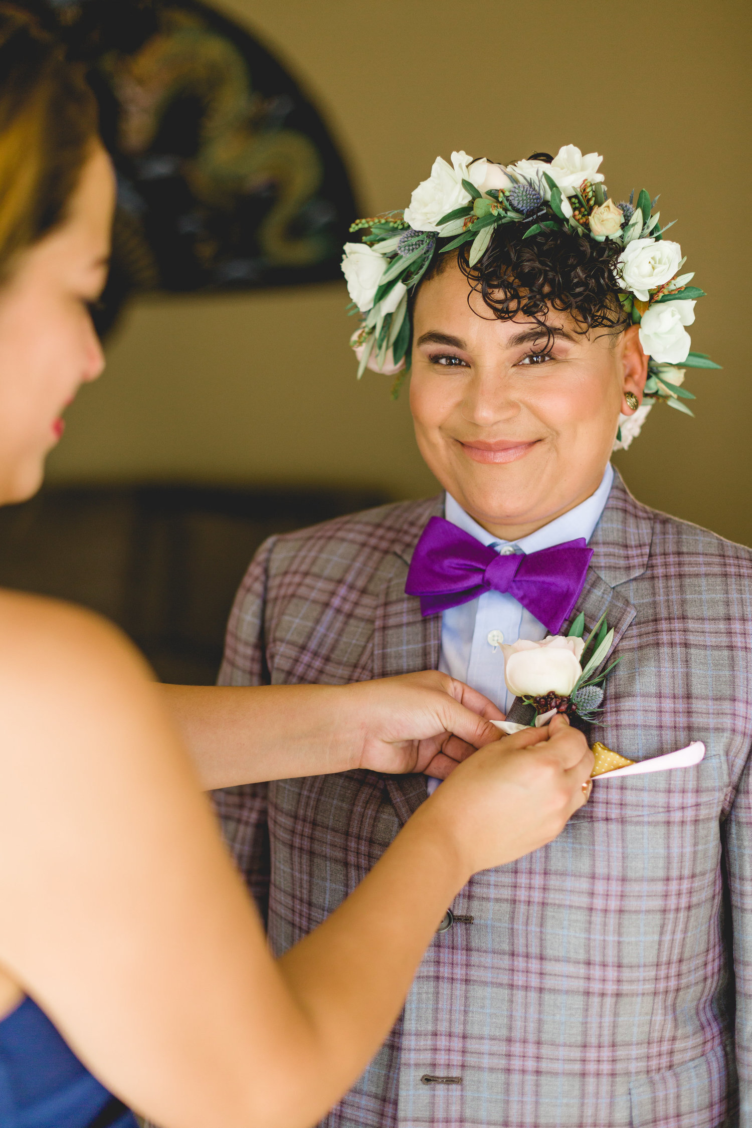 roz getting ready in suit and flower crown before wedding ceremony at redwoods sanctuary in California