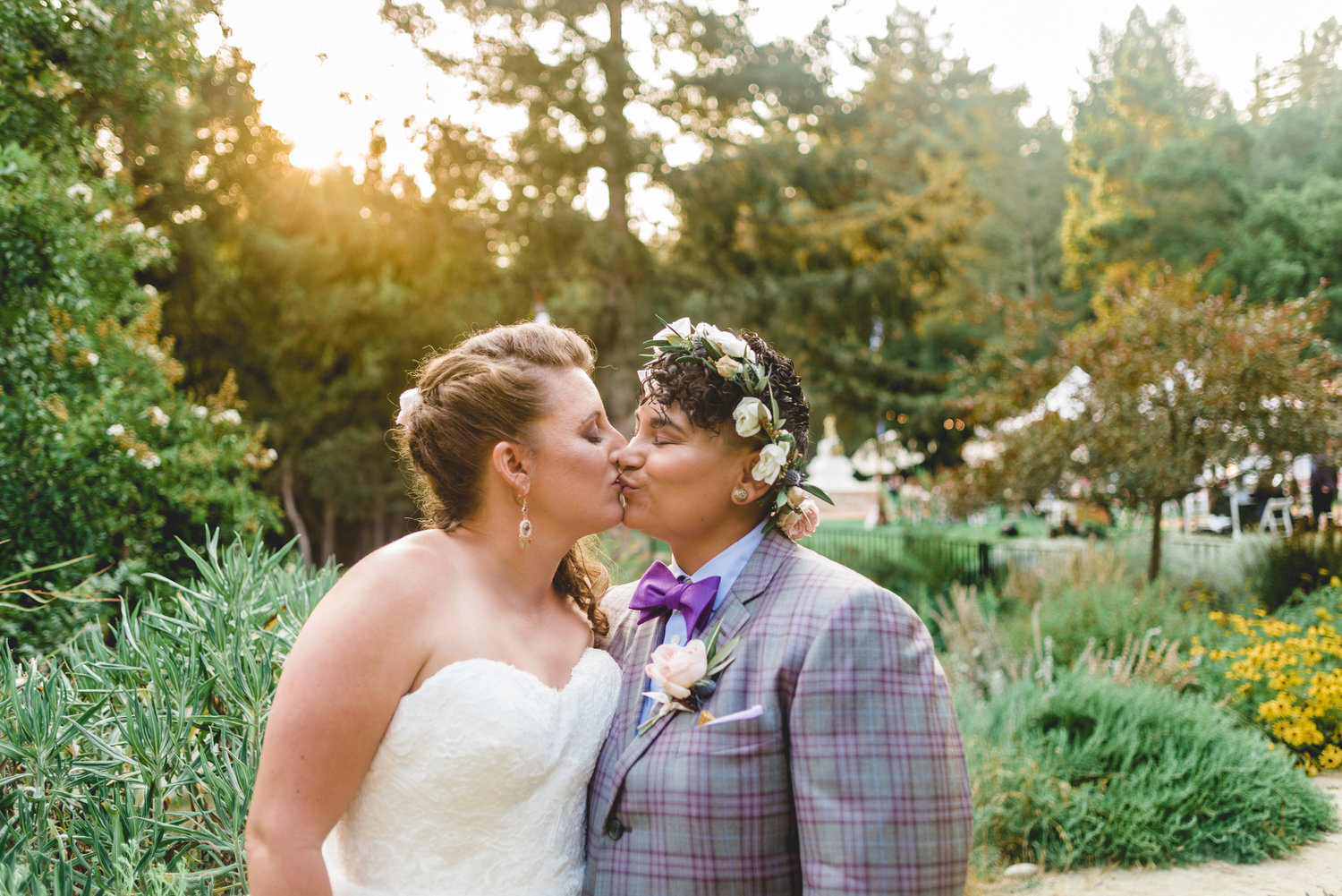 Carrie and roz kissing before their wedding ceremony at redwoods sanctuary in california