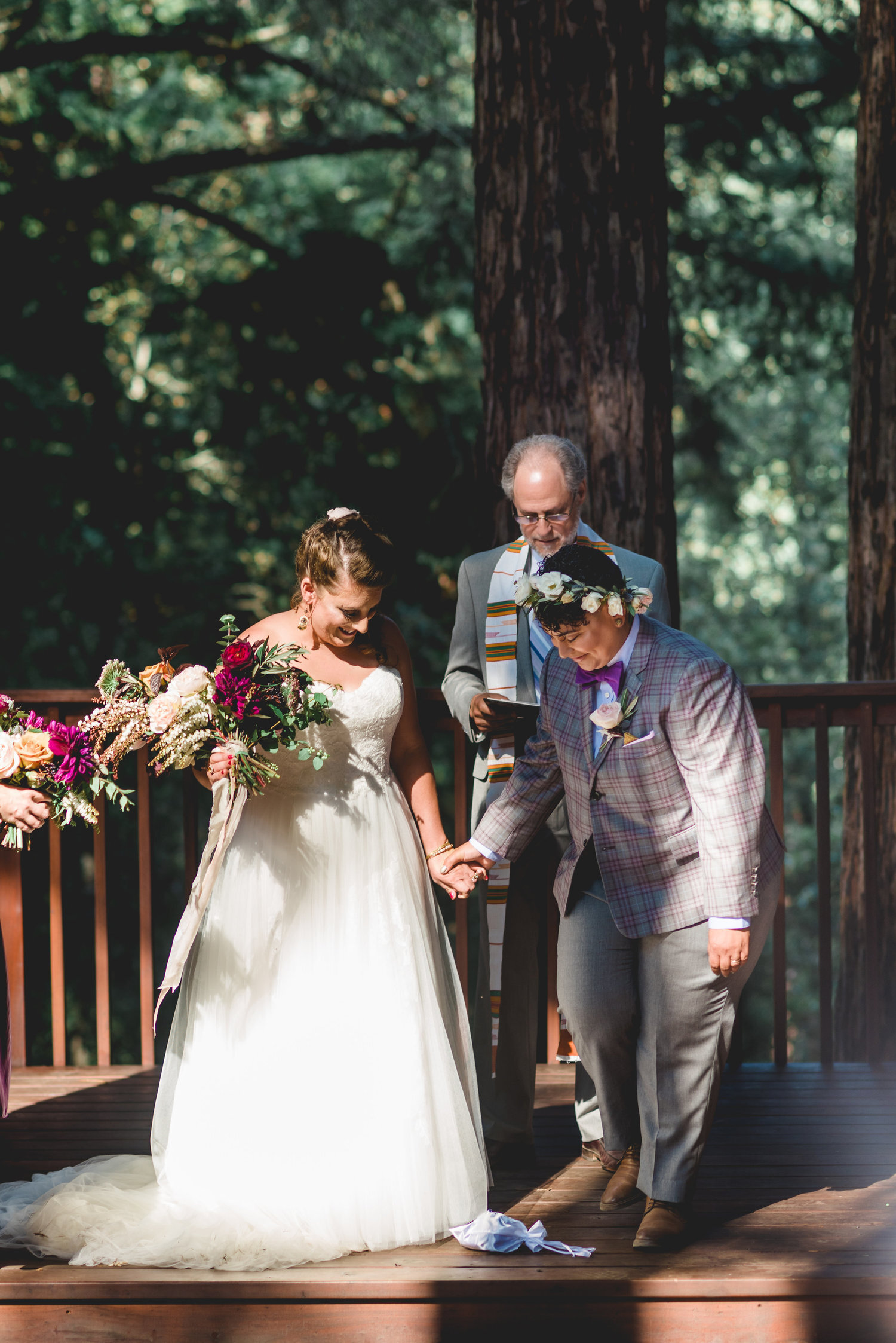 roz and carrie smashing the glass to reflect Carrie's jewish heritage at wedding ceremony in redwoods California