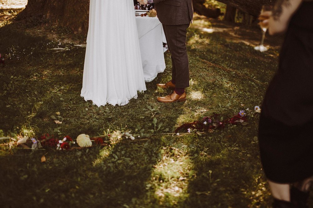 Alex and Frances stand in a ring of flowers during their wedding ceremony at a campsite in Spring Green, Wisconsin