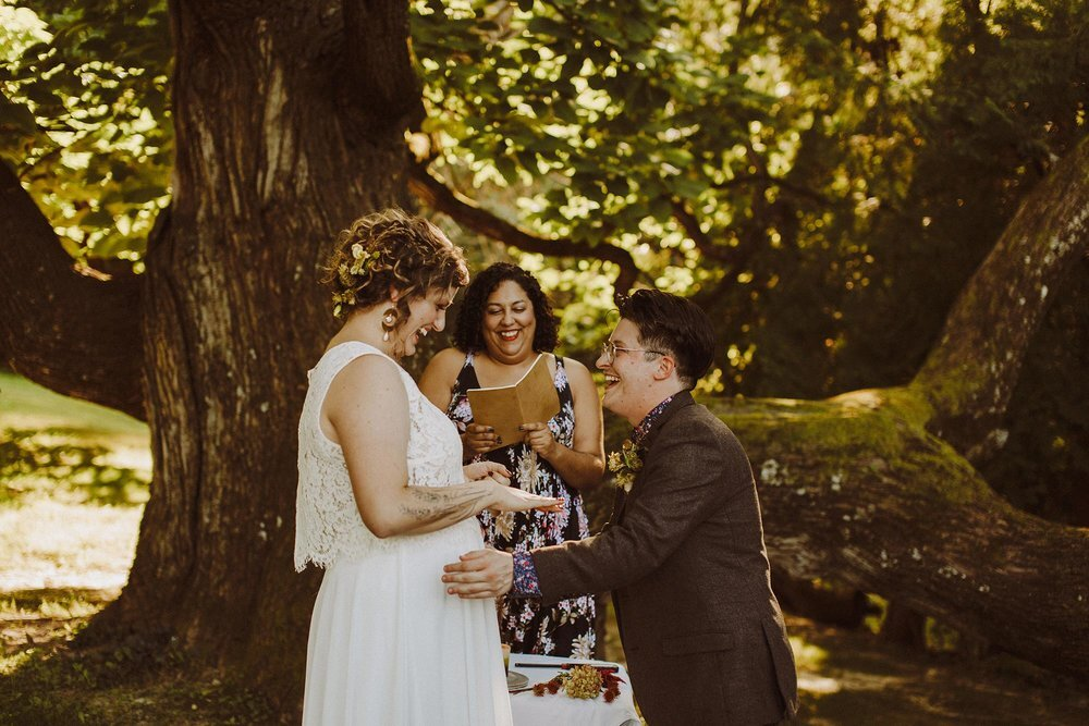 Alex and Frances exchanging rings and vows during wedding ceremony at campsite in Spring Green, Wisconsin
