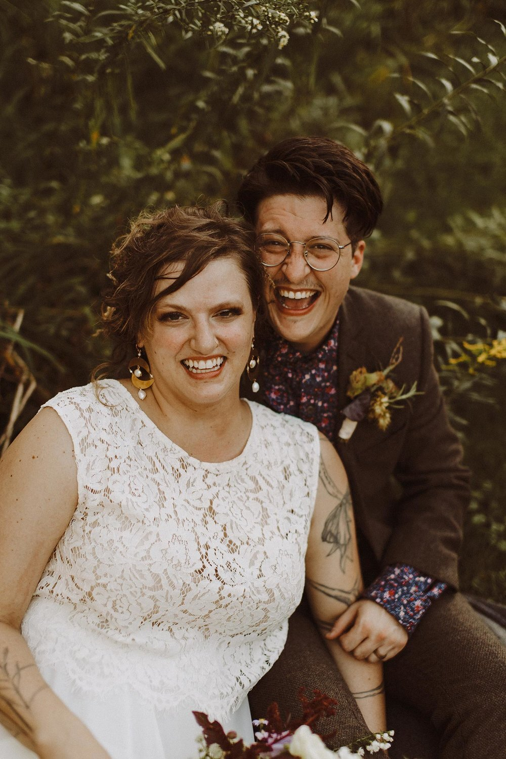 Newlyweds embrace and smile after wedding ceremony at campsite in Spring Green, Wisconsin