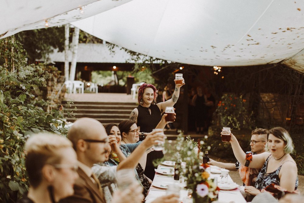 Guests give a toast under a tent at this campsite wedding reception in Spring Green, Wisconsin
