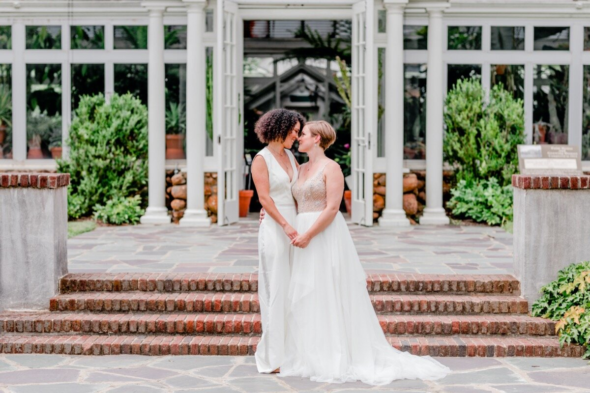 Celestial and Geode wedding inspiration in Winston Salem NC showing two brides in wedding dress and jumpsuit in front of greenhouse Ariel Kaitlin Photography