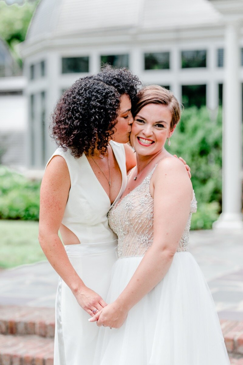 Celestial and Geode wedding inspiration in Winston Salem NC showing two brides in wedding dress and jumpsuit kissing in front of greenhouse Ariel Kaitlin Photography