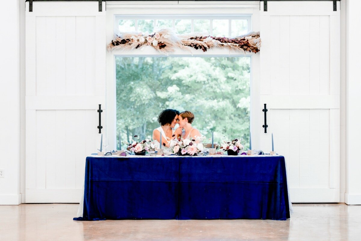 Celestial and Geode wedding inspiration in Winston Salem NC showing two brides leaning in for kiss at head reception table Ariel Kaitlin Photography