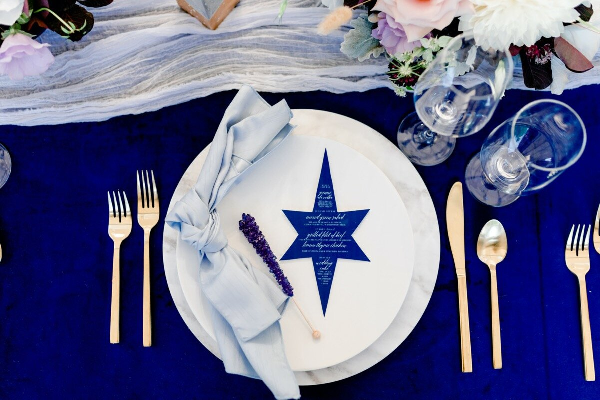Celestial and Geode wedding inspiration in Winston Salem NC showing cobalt blue and gold star menu and table setting Ariel Kaitlin Photography