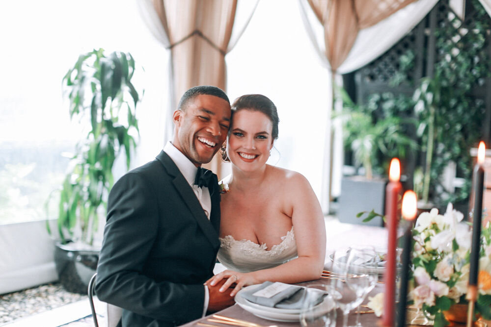 newlywed bride and groom smile at head table during nyc rooftop wedding reception Amber Marlo Photography