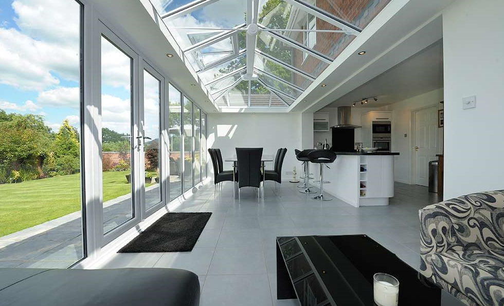 This development although the roof is over 75% translucent and has over 50% translucent walls would not be considered a conservatory due to not being separated from the main house. In this case this development is not exempt of building regulations.