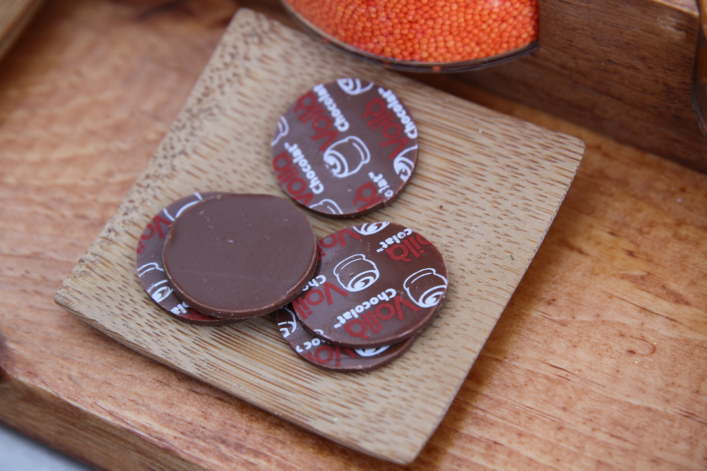 """Plaquettes (literally, """"small plaques"""" in French) are small circles of chocolate with your logo or design, which can be used to top round chocolates like truffles."""