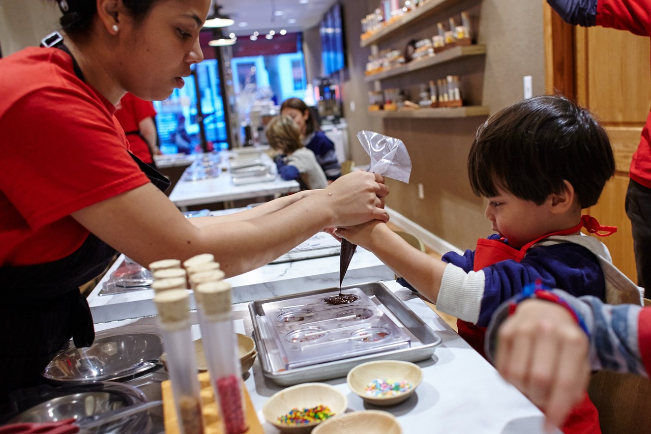 Life is sweet indeed at Voilà Chocolat: Anna Urena helps Bailey Chou Almeraz make lollipops. STEVE REMICH FOR THE WALL STREET JOURNAL