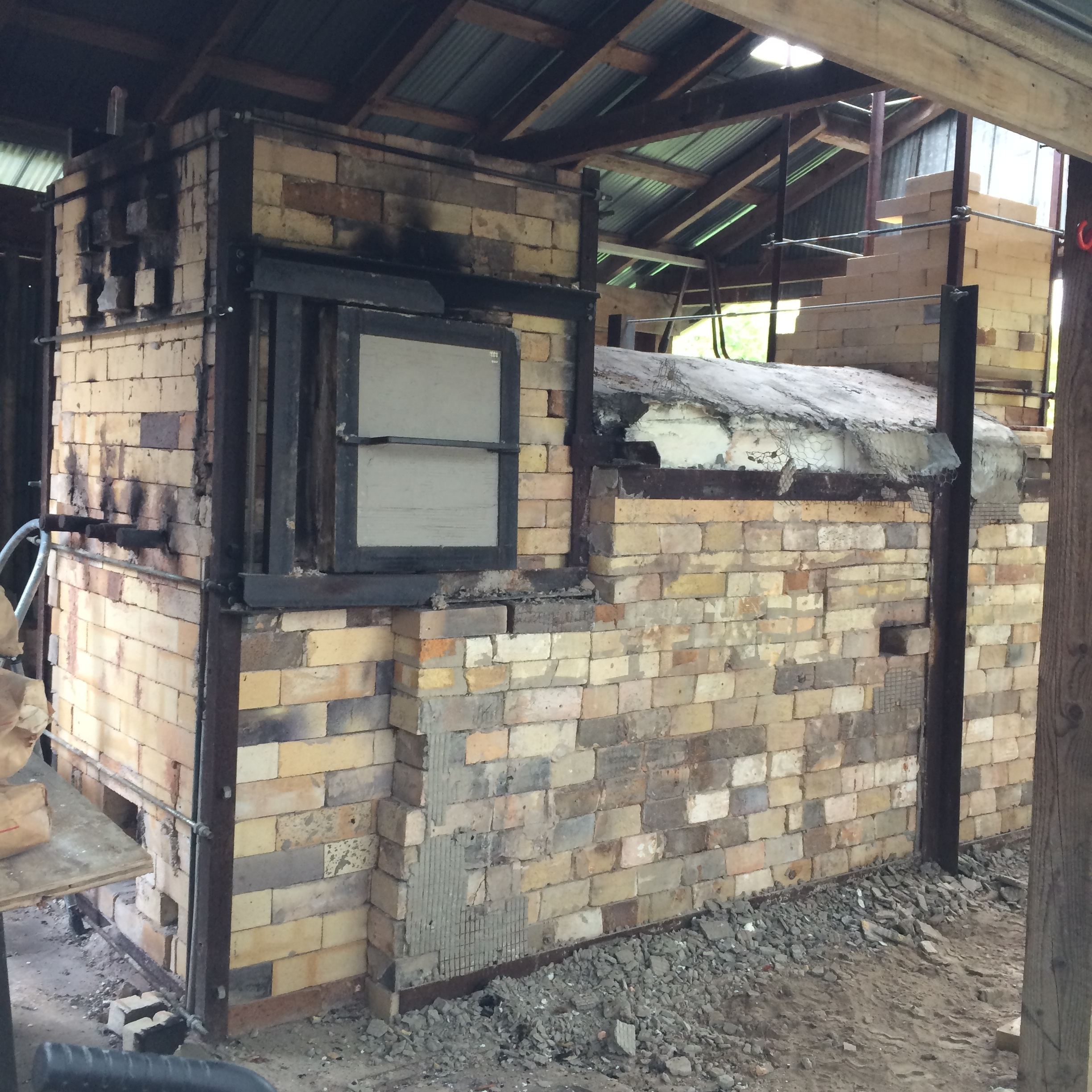 Step 1: Take down the chimney. Here's the train kiln, with chimney almost down, and after the outer layer of chicken wire and concrete was removed (with Jesse's super handy pneumatic hammer).