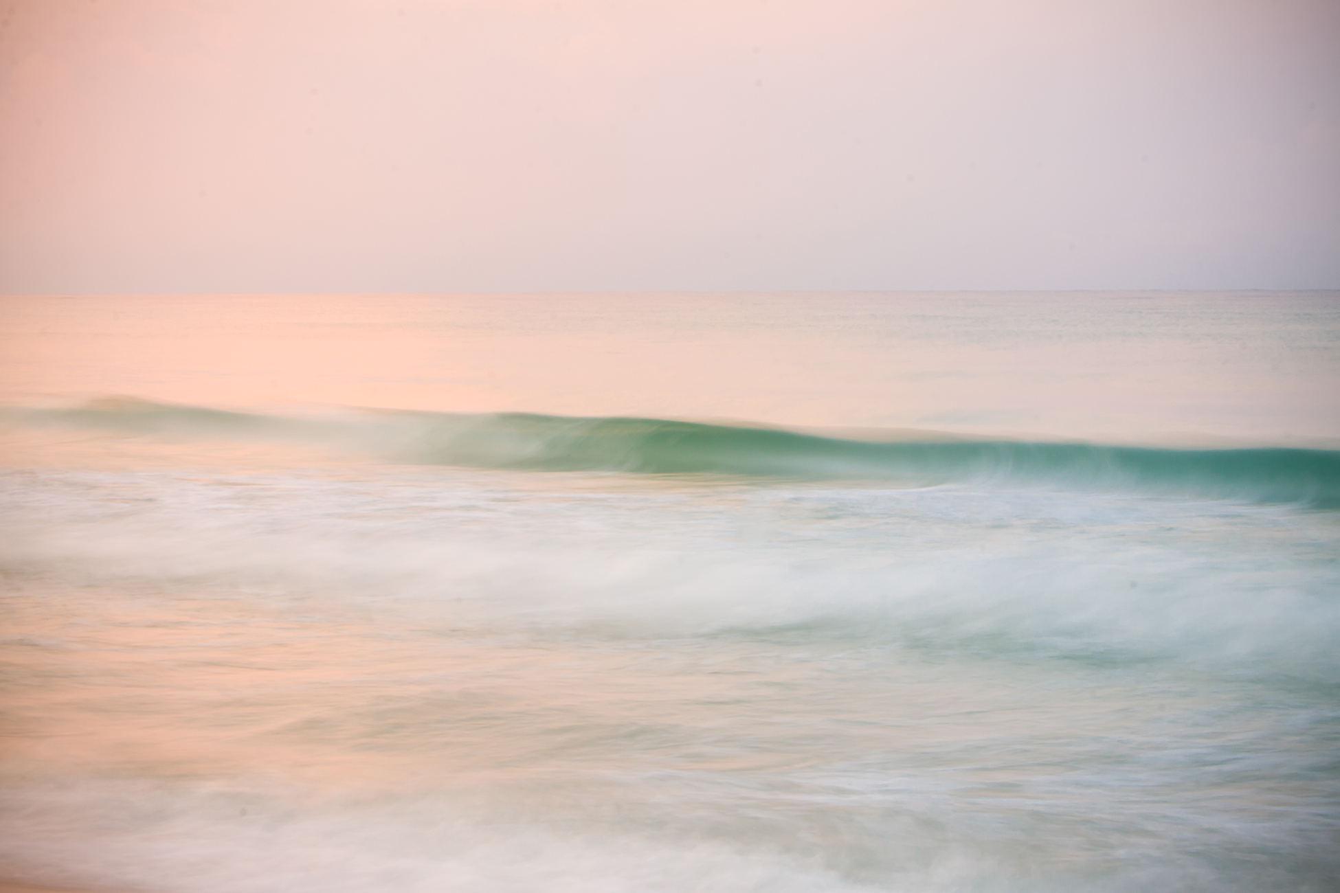 Colorful sunrise reflected in a moving wave.